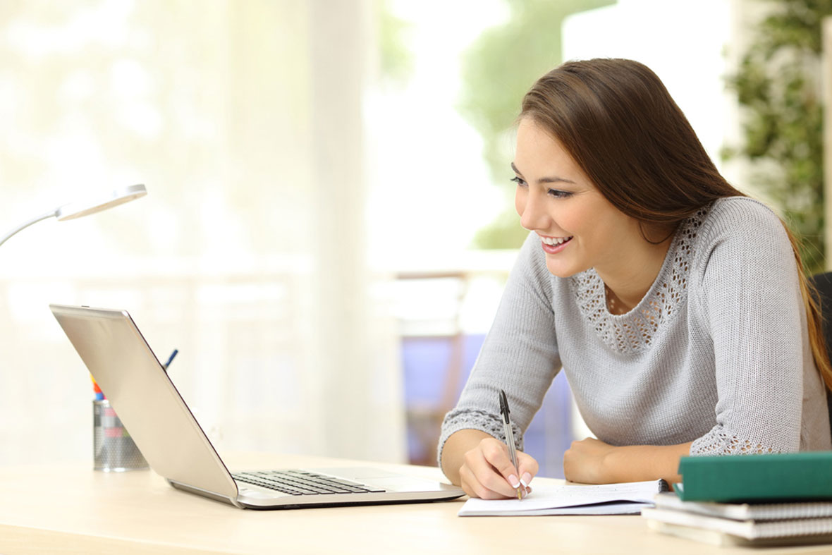 Lady matched betting on her laptop taking notes earning money from home online